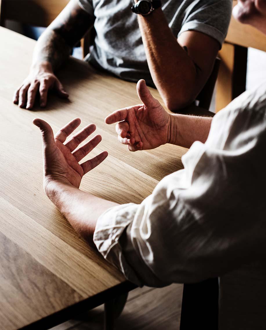 Man gestikuliert friedlich bei Gespräch an Tisch