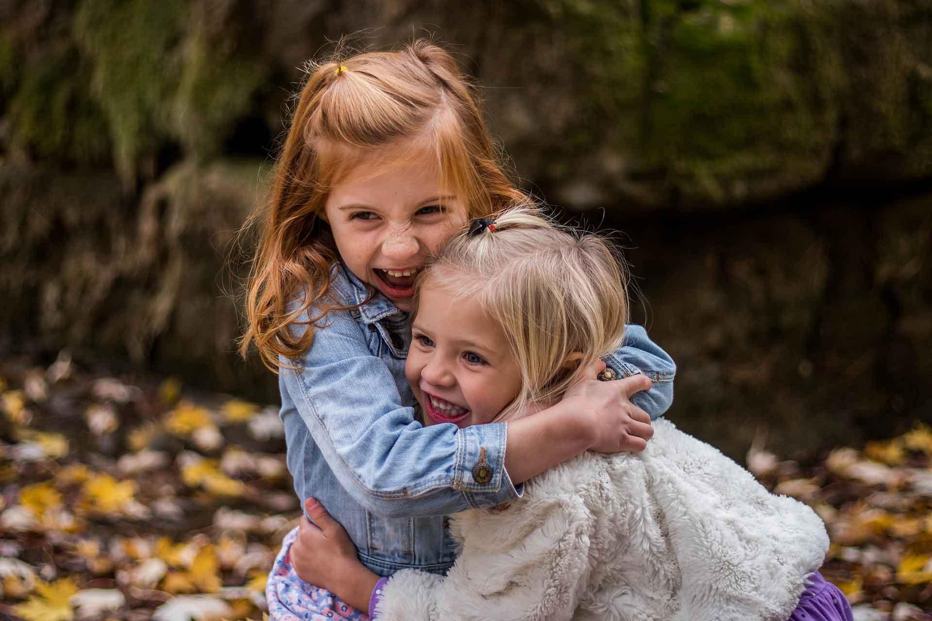 zwei junge Mädchen umarmen einander