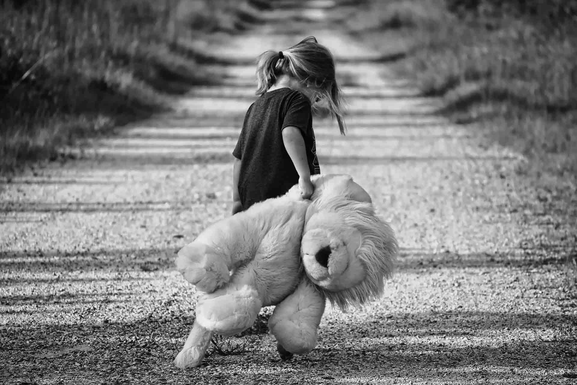 Kind mit Plüschtier geht auf Strasse