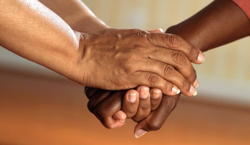 Hände von zwei Personen, die einander halten