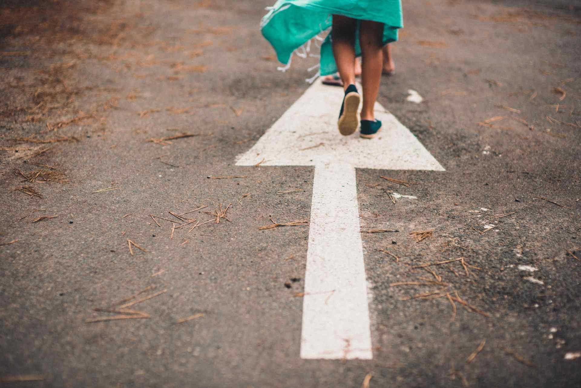 Frau geht auf Straße mit Pfeil