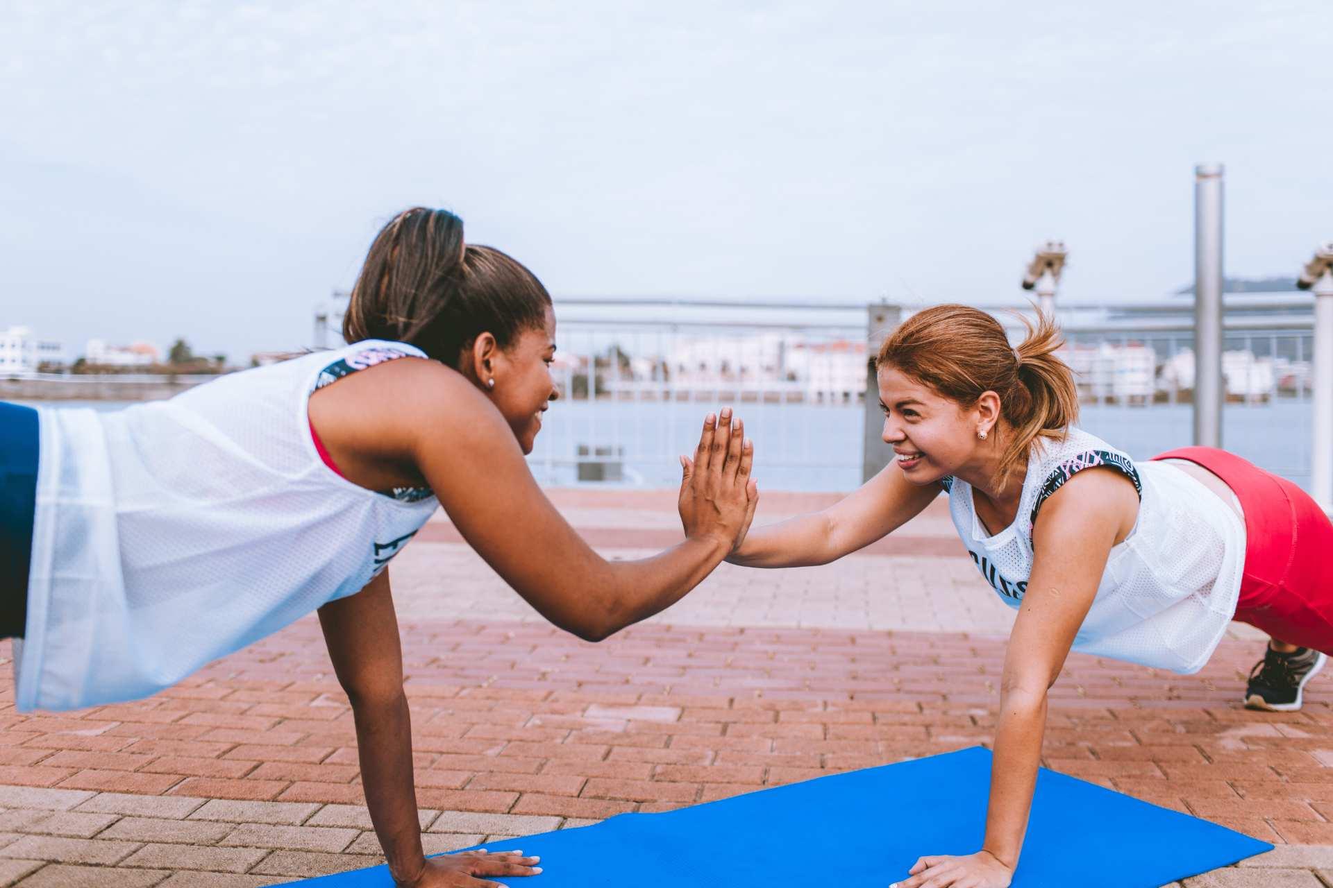 Zwei Frauen machen Liegestütz und Handklatsch