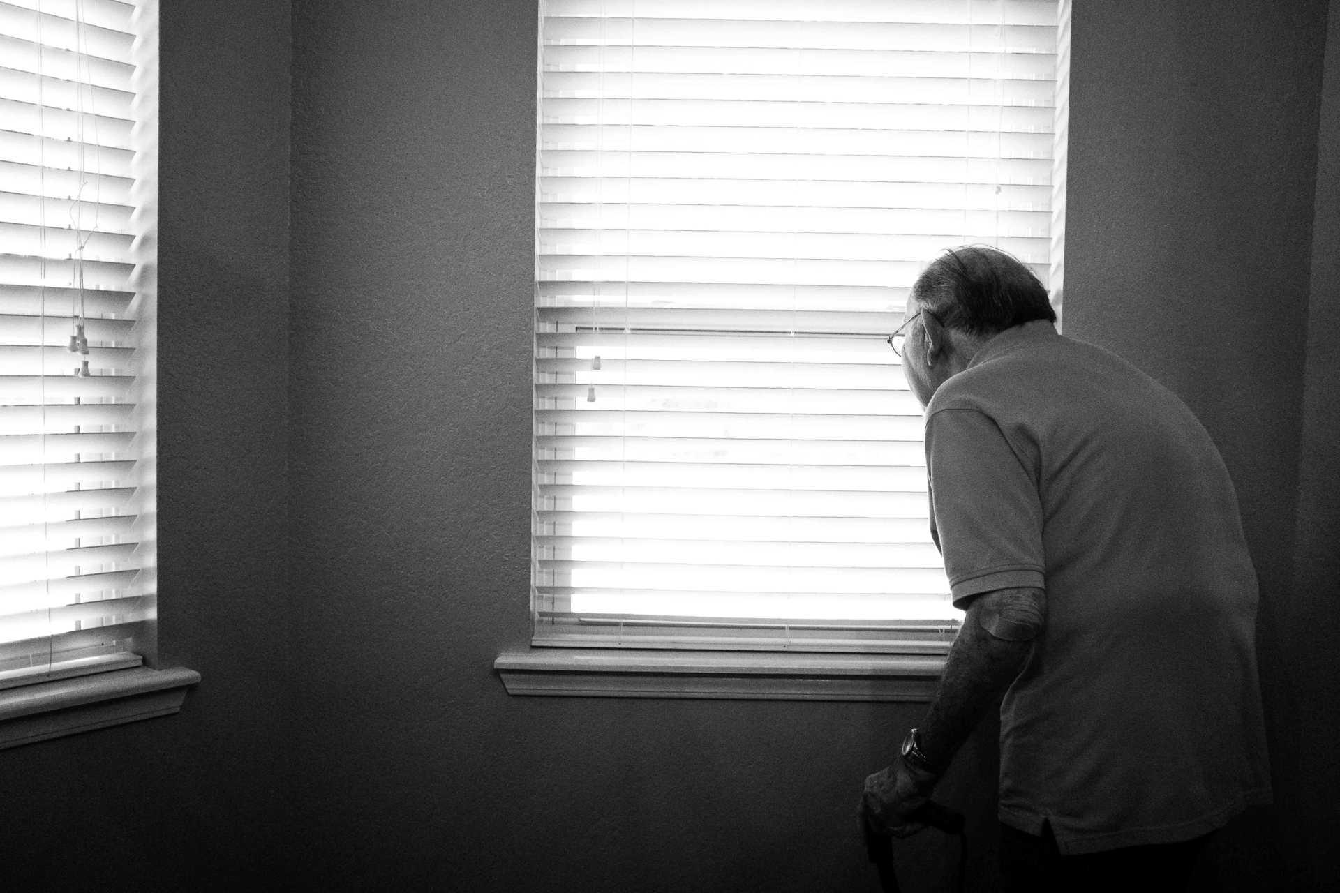 Alter Mann steht beim Fenster