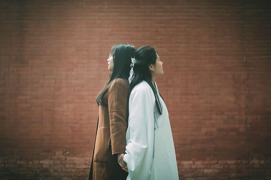Zwei Frauen stehen Rücken an Rücken