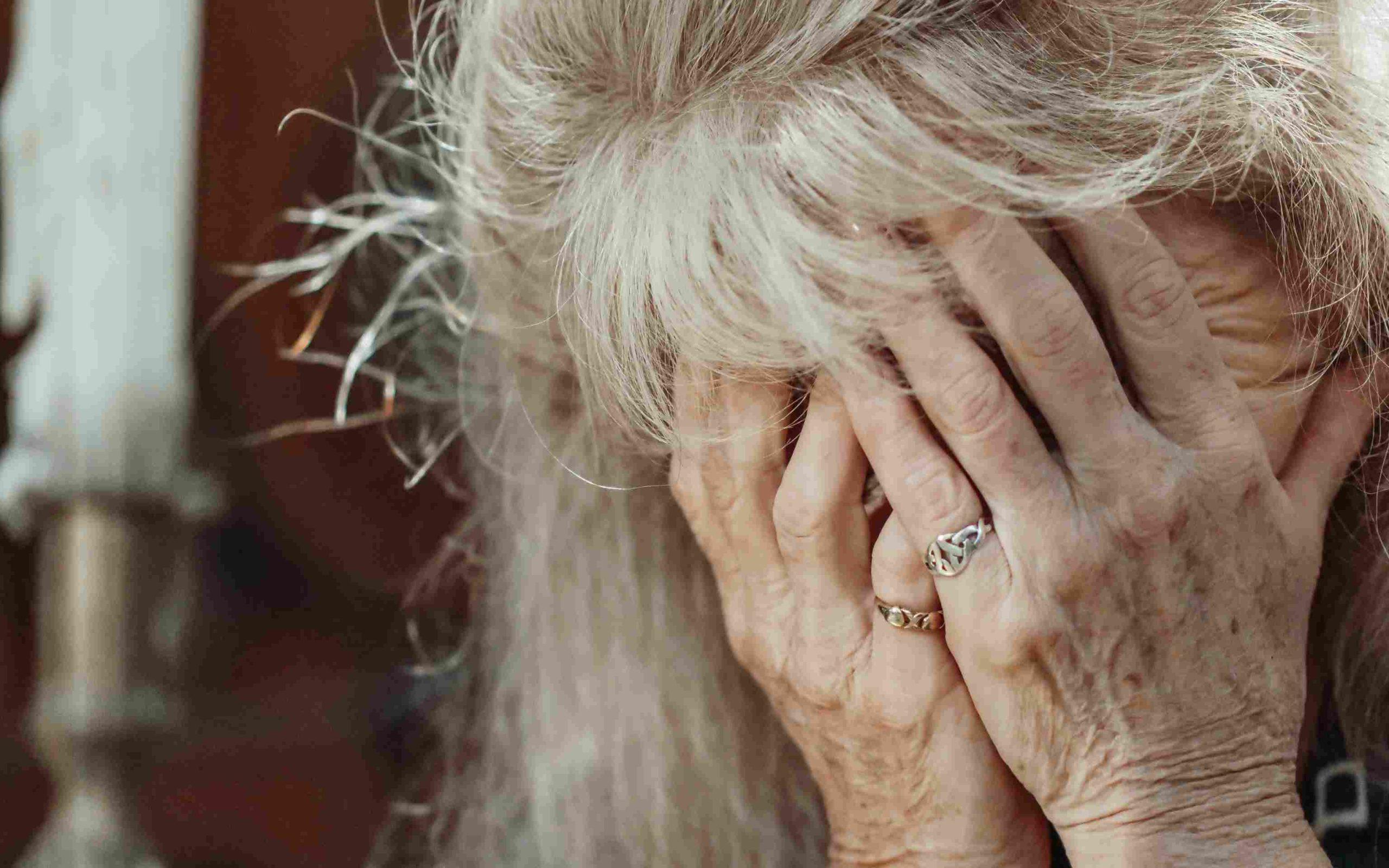 Alte Frau hält Hände vor das Gesicht