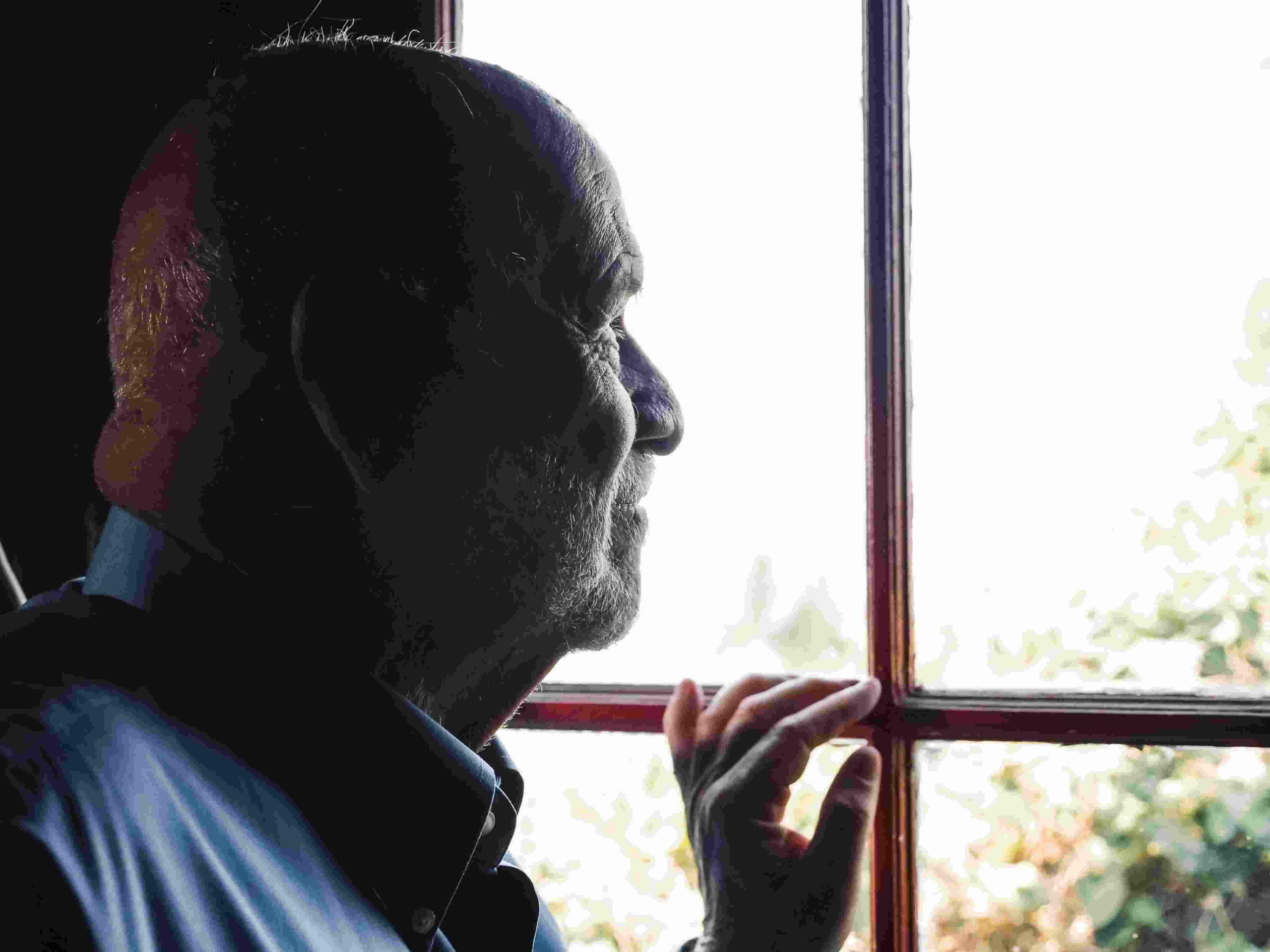 Alter Mann schaut aus dem Fenster