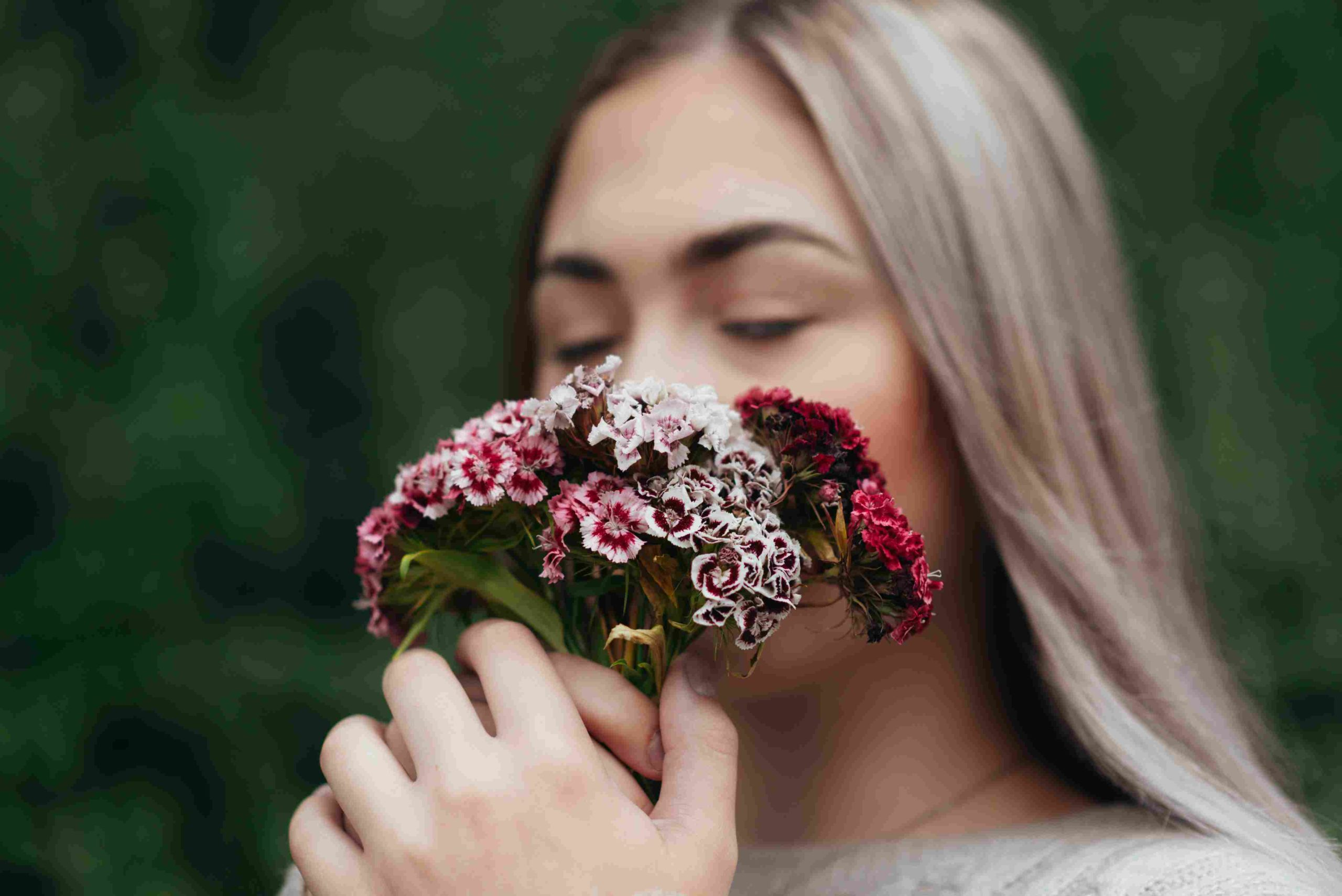 Frau riecht an Blumen